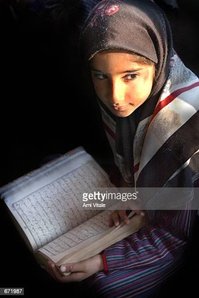 Kashmiri girl reads the Koran during Ramadan prayers November 18 2001 at a shrine in the summer capital of Srinagar Kashmir India The war in Kashmir...