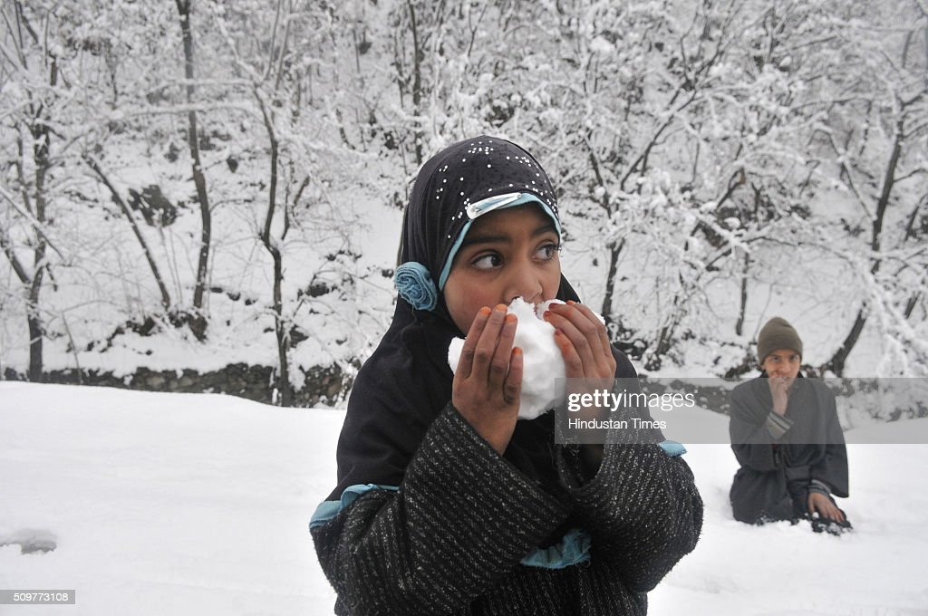 A Kashmiri girl tasting fresh snow on February 12, 2016 on the outskirts of Srinagar, India. Incessant snowfall and rains on Thursday led to the closure of the valleys arterial Srinagar-Jammu National Highway and brought relief from a long spell of dry weather in Kashmir.