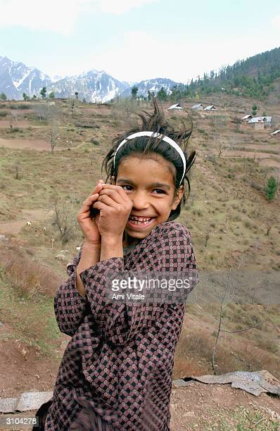 Kashmiri girl who was watching her families sheep laughs as she stands in her village of Nambla that lies along the Line of Control in Indian Kashmir...