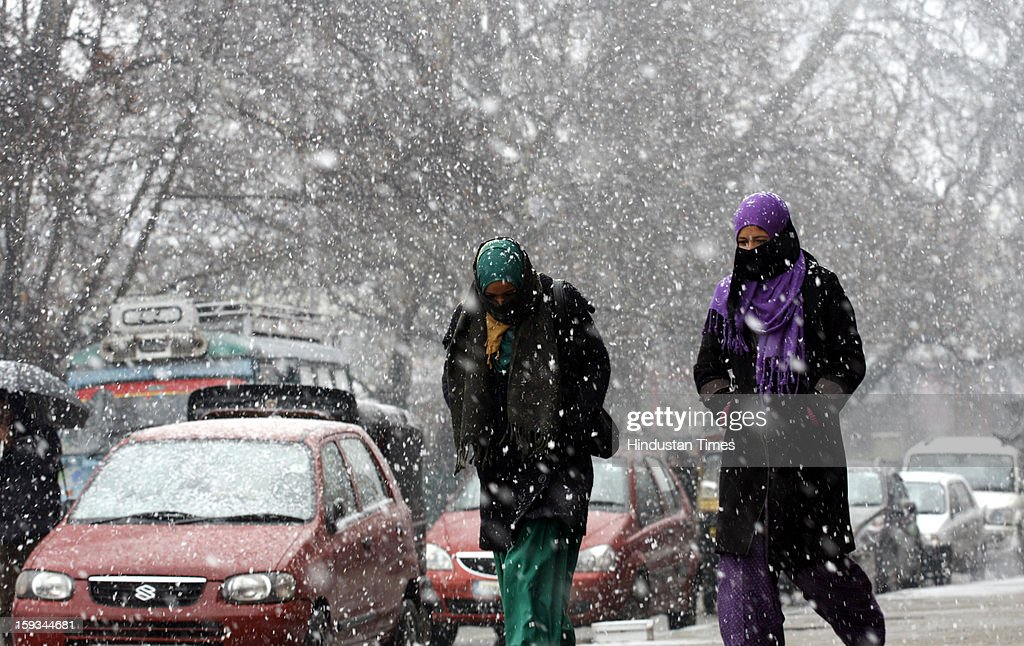 Kashmiri girls walk during a fresh snowfall on January 12, 2013 in Srinagar, India. The Kashmir Valley experienced fresh snowfall today, forcing authorities to close the Srinagar-Jammu highway.