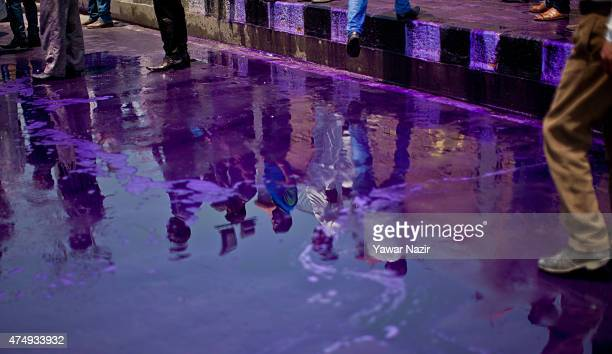 Kashmiri government daily wage employees are reflected in the purple dyed chemical water which was used by Indian police at the employees during a...
