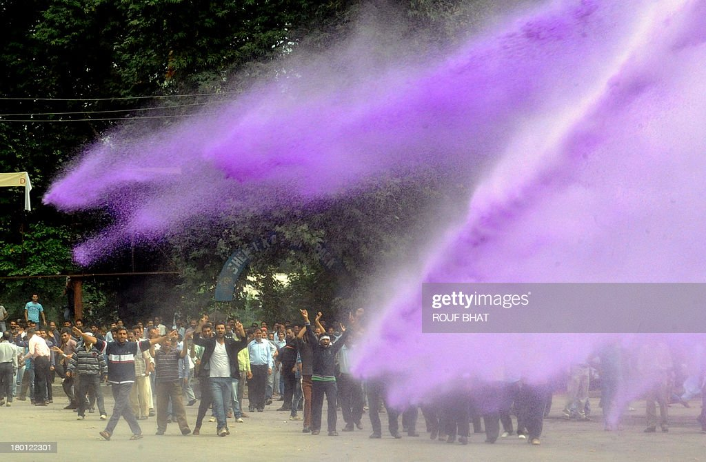 Kashmiri government employees demonstrate as riot police spray purple-dyed water cannon in Srinagar on September 9, 2013. Indian police detained dozens of government employees, who have been demanding regularisation of contractual jobs and an increase in retirement age.They also demanded an impartial probe into the killing of four people by Indian paramilitary soldiers on September 7,and killers should be exposed. AFP PHOTO/Rouf BHAT