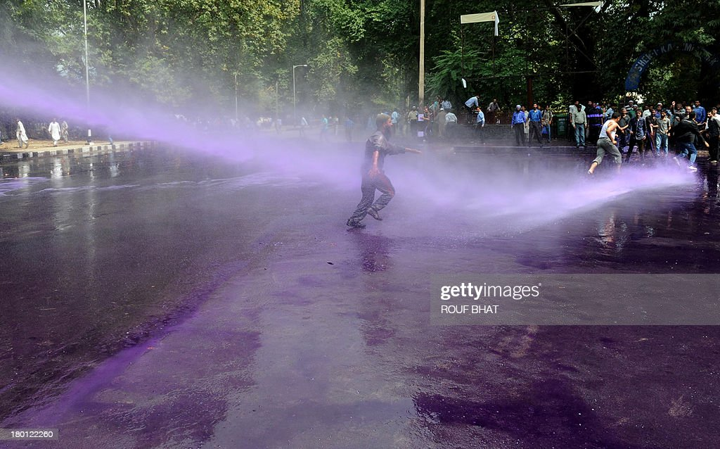 Kashmiri government employees run during a protest as riot police spray purple-dyed water cannon in Srinagar on September 9, 2013. Indian police detained dozens of government employees, who have been demanding regularisation of contractual jobs and an increase in retirement age.They also demanded an impartial probe into the killing of four people by Indian paramilitary soldiers on September 7,and killers should be exposed. AFP PHOTO/Rouf BHAT