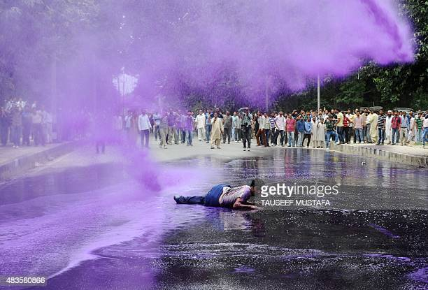 Kashmiri government employees shout slogans as purpledyed water is sprayed by security personnel during a protest in Srinagar on August 10 2015...
