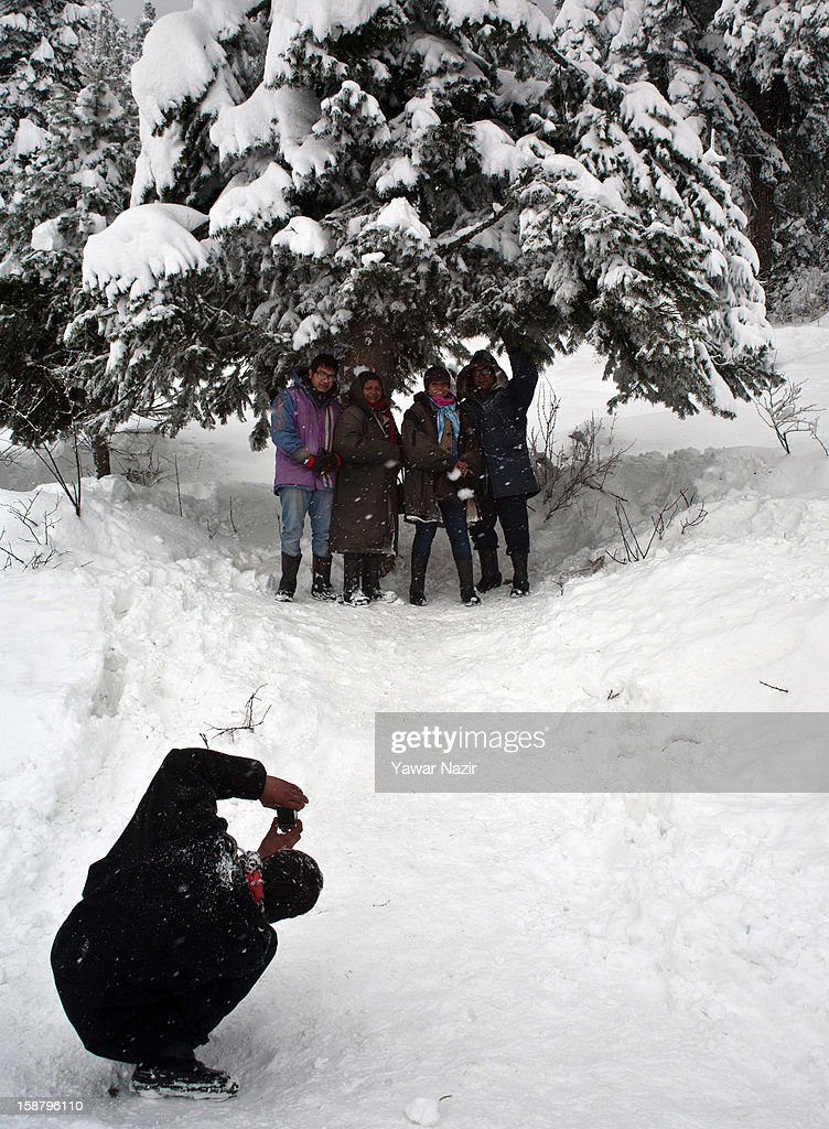 A Kashmiri guide takes pictures of tourists during a snowfall on December 29, 2012 in Gulmarg, 54 km (35 miles) to the west of Srinagar, the summer capital of Indian-administered Kashmir, India. With the second round of heavy snowfall in Kashmir valley, skiers from around the globe have descended on the ski resort of Gulmarg, known for long-run skiing, snow-boarding, heli-skiing and steep mountains. Gulmarg is located less than six miles from the ceasefire line or Line of Control (LoC) that divides Kashmir between India and Pakistan. As a sense of normalcy has started to return to this strife-torn region, various foreign governments, including the United Kingdom, have lifted the travel advisory to its citizens traveling to Kashmir, raising the hopes of the local tourism industry, officials said.