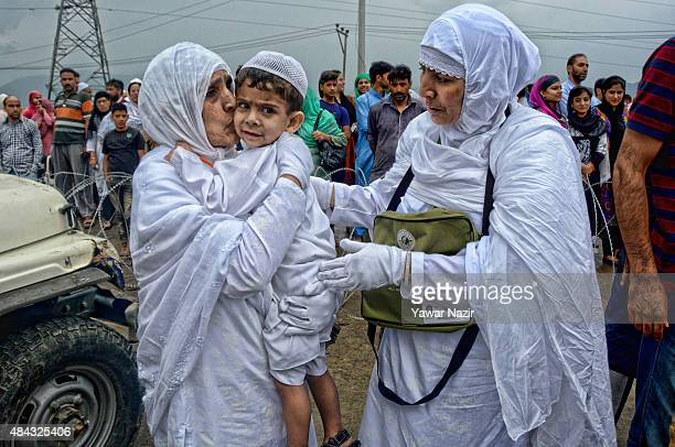 Kashmiri Hajj pilgrims kiss a their young relative before boarding a bus which is departing for the annual Hajj pilgrimage on August 17 2015 in...