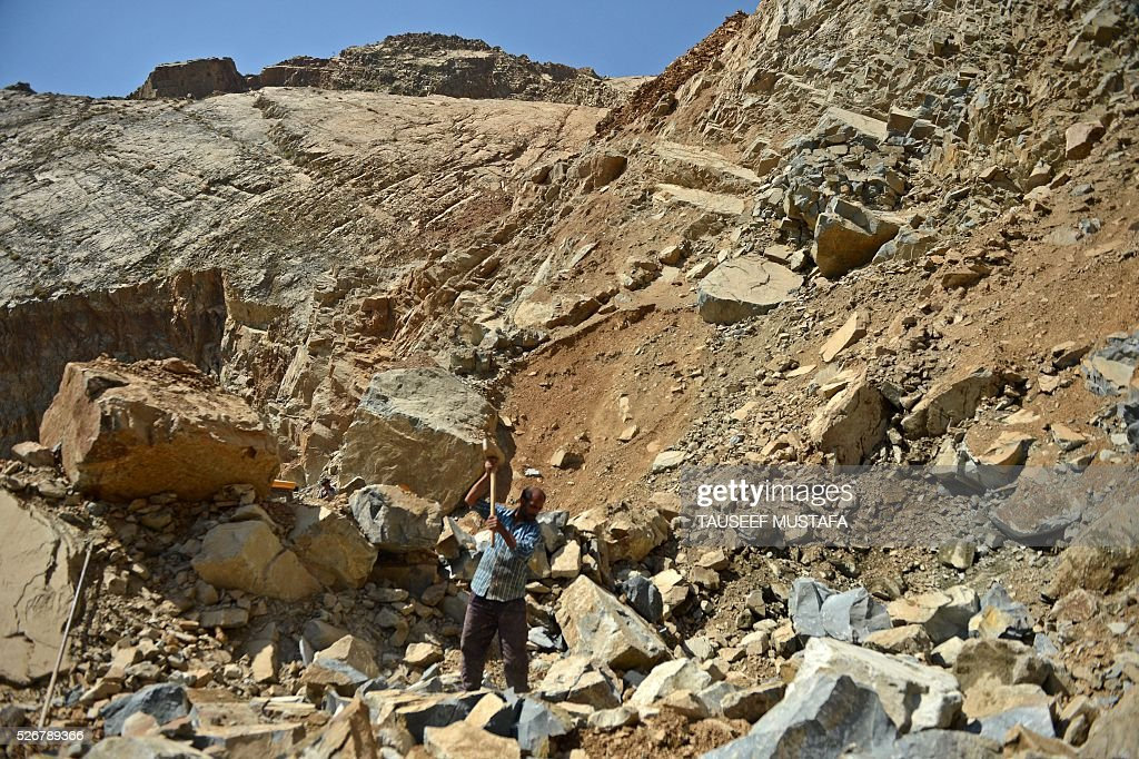 A Kashmiri labourer breaks rocks inside a stone quarry on the outskirts of Srinagar on May 1, 2016, on International Labour Day. International Labour Day or May Day is celebrated across the world annually on May 1. / AFP / TAUSEEF