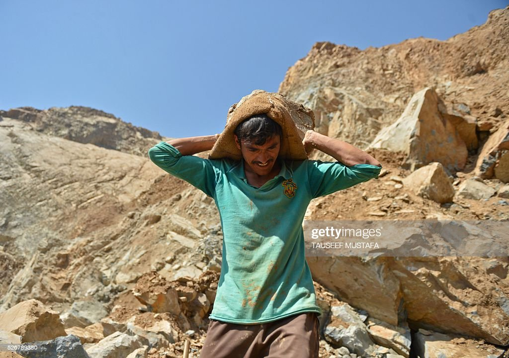 A Kashmiri labourer carries a sackful of rocks inside a stone quarry on the outskirts of Srinagar on May 1,2016, on International Labour Day. International Labour Day or May Day is celebrated across the world annually on May 1. / AFP / TAUSEEF