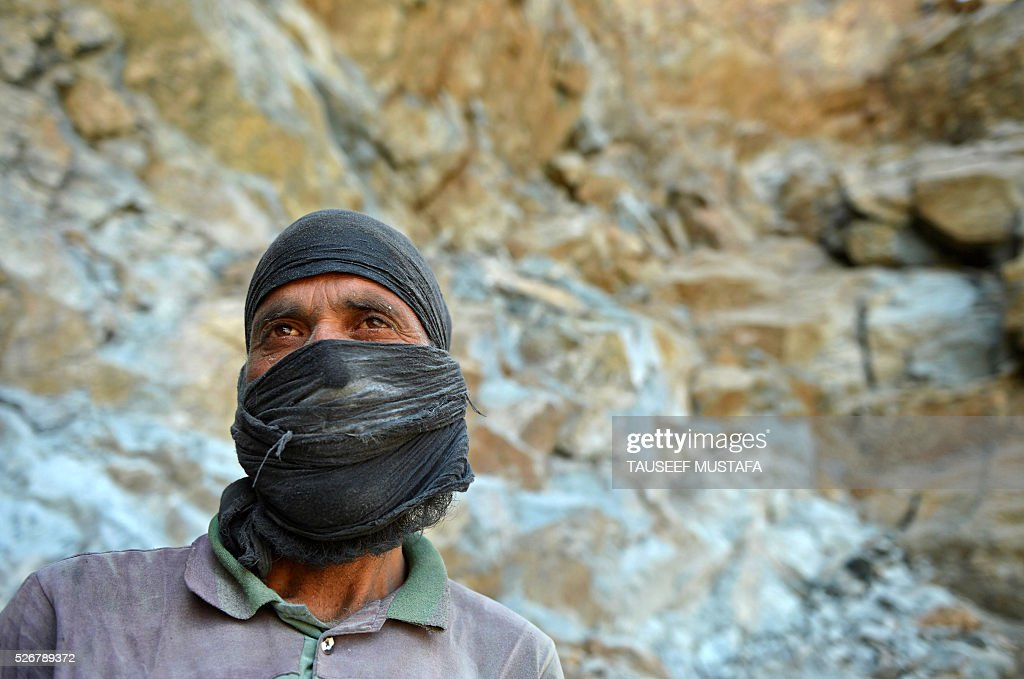 A Kashmiri labourer poses as he takes a break from extracting rocks inside a stone quarry on the outskirts of Srinagar on May 1, 2016, on International Labour Day. International Labour Day or May Day is celebrated across the world annually on May 1. / AFP / TAUSEEF