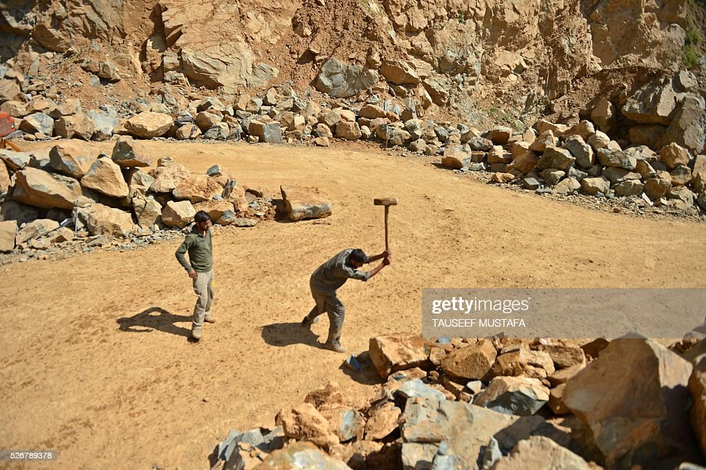 Kashmiri labourers break rocks inside a stone quarry on the outskirts of Srinagar on May 1, 2016, on International Labour Day. International Labour Day or May Day is celebrated across the world annually on May 1. / AFP / TAUSEEF