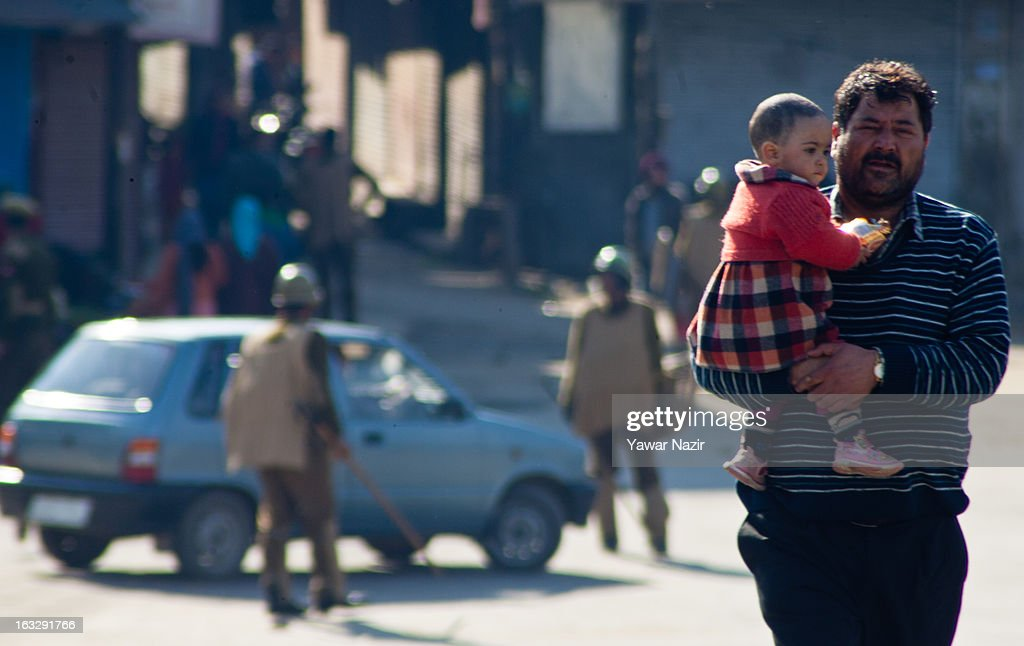 A Kashmiri man carries a baby as Indian policemen stopsa car during a curfew-like restriction on March 7, 2013 in Srinagar, the summer capital of Indian Administered Kashmir, India. Clashes erupted in most parts of Kashmir today leaving scores of people injured. Meanwhile Indian authorities imposed curfew-like restrictions for the second consecutive day in most parts of Kashmir following the killing of a Kashmiri youth by the Indian army in North Kashmir's Baramulla district.