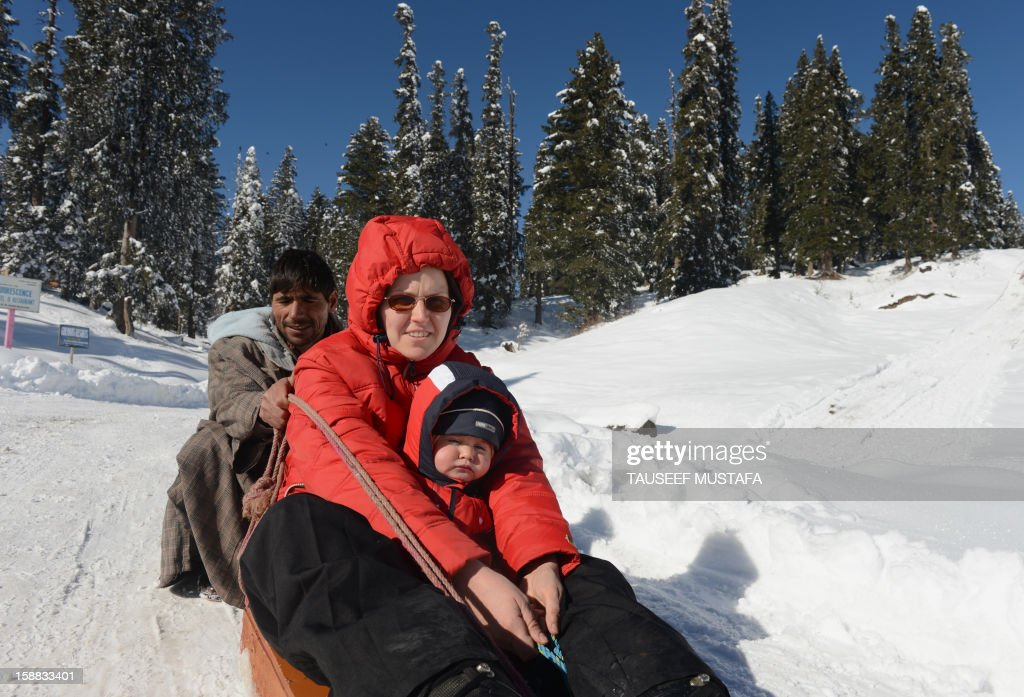 A Kashmiri man guides a sleigh carrying foreign tourists in Gulmarg, about 55 kms north of Srinagar, on December 31, 2012. Gulmarg is the main ski destination in Indian Kashmir and hundreds of foreigners visit the slopes despite an ongoing insurgency in the region. AFP PHOTO/ Tauseef MUSTAFA