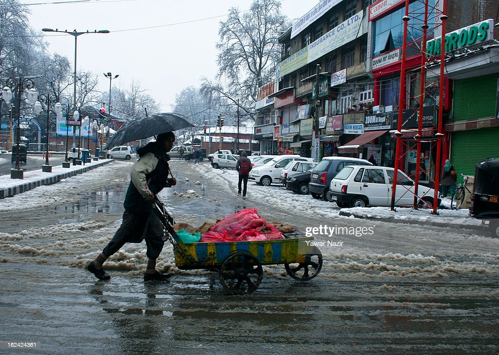A Kashmiri man holds an umbrella as he walks with his hand cart after snowfall on February 23, 2013 in Srinagar, Indian Administered Kashmir, India. Several parts of the Kashmir Valley, including the summer capital Srinagar, experienced fresh snowfall today, prompting the authorities to issue an avalanche warning and leading to closure of the Jammu-Srinagar Highway, the only road link between Kashmir and rest of India.