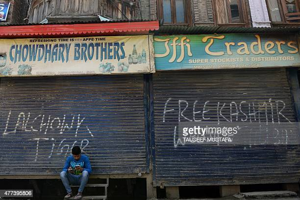 A Kashmiri man looks at his mobile phone in front of shuttered shops in Srinagar on June 17 2015 during a oneday strike called by seperatist groups...