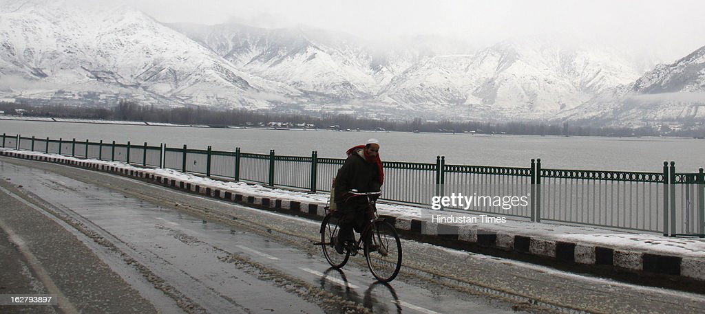 A kashmiri man padels a bicycle after a fresh snow fall on February 27, 2013 in Srinagar, India. Kashmir valley was hit by a fresh spell of rains and snow during the preceding night of February 26 and 27.