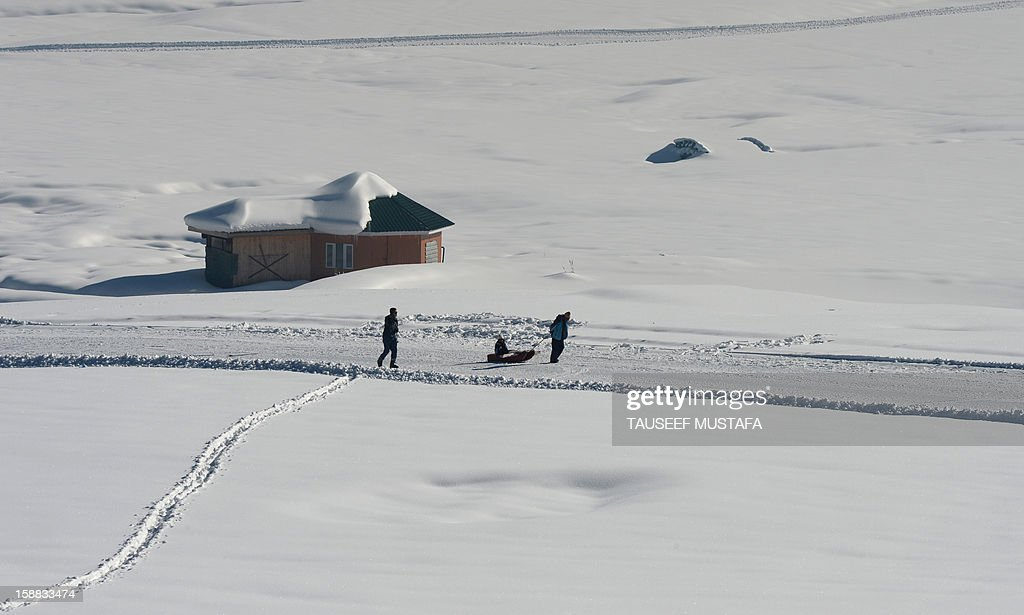 A Kashmiri man pulls a sleigh carrying Indian tourists in Gulmarg, about 55 kms north of Srinagar, on December 31, 2012. Gulmarg is the main ski destination in Indian Kashmir and hundreds of foreigners visit the slopes despite an ongoing insurgency in the region.AFP PHOTO/ Tauseef MUSTAFA