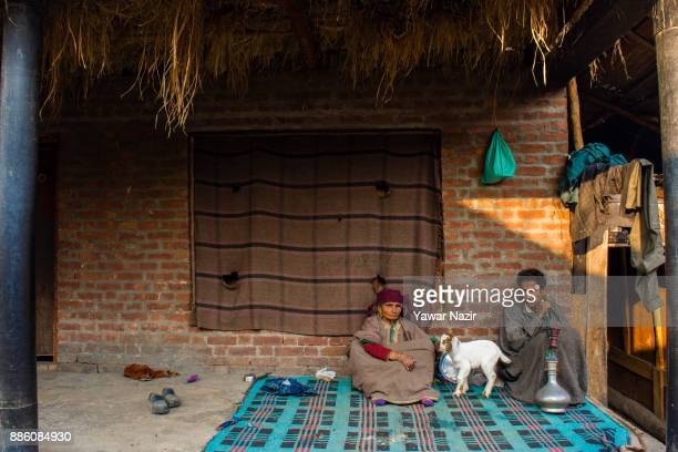 Kashmiri man sits with his mother and a goat on the porch of his house in a village on December 05 2017 in Pattan north of Srinagar the summer...