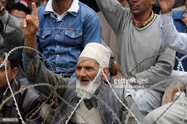 A Kashmiri man sitting behind a barbed wire fence gestures as he listens to a speech by Farooq Abdullah the former state chief minister and patron of...