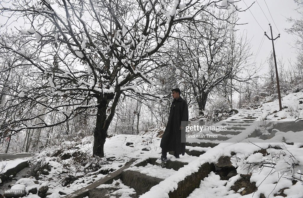 Kashmiri man walks down on a snow covered steps on hilly terrain on February 12, 2016 on the outskirts of Srinagar, India. Incessant snowfall and rains on Thursday led to the closure of the valleys arterial Srinagar-Jammu National Highway and brought relief from a long spell of dry weather in Kashmir.