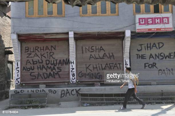 Kashmiri man walks next to graffiti that reads to the militant commanders during curfew in Lal Chowk area on July 8 2017 in Srinagar India...