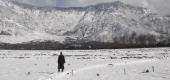 A kashmiri man walks on snow covered field with a back drop of snow decked mountain during a fresh snow fall on February 16 2014 in Srinagar India...