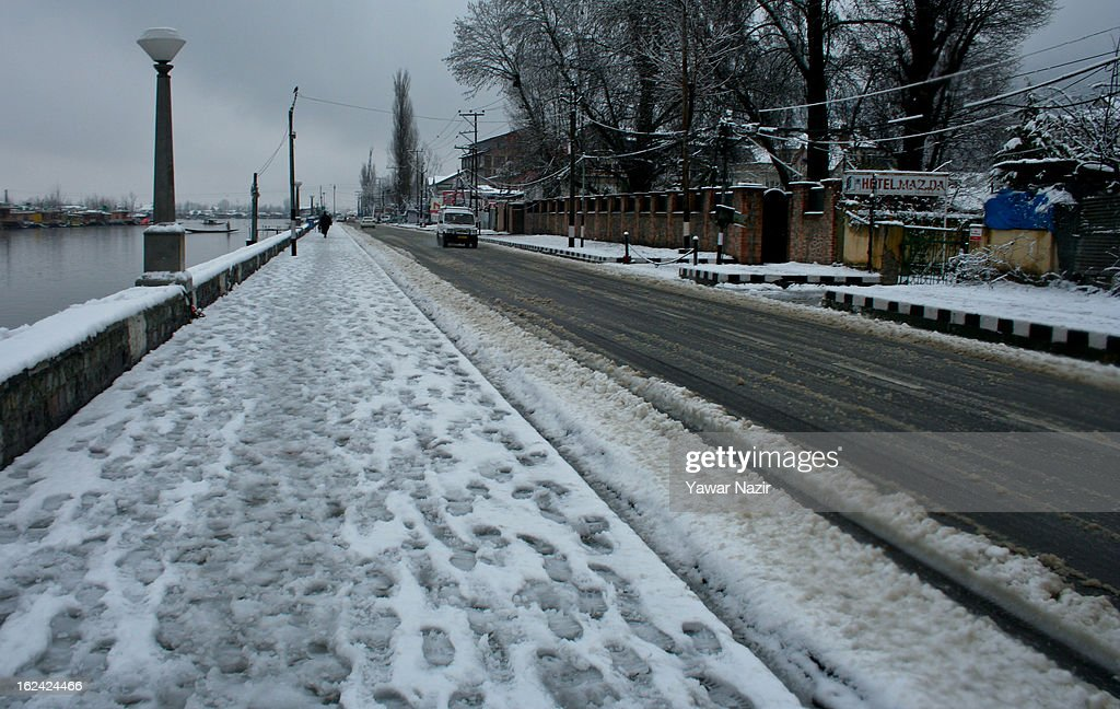 Kashmiri man walks on the footpath on the bank of Dal lake after a snowfall on February 23, 2013 in Srinagar, Indian Administered Kashmir, India. Several parts of the Kashmir Valley, including the summer capital Srinagar, experienced fresh snowfall today, prompting the authorities to issue an avalanche warning and leading to closure of the Jammu-Srinagar Highway, the only road link between Kashmir and rest of India.