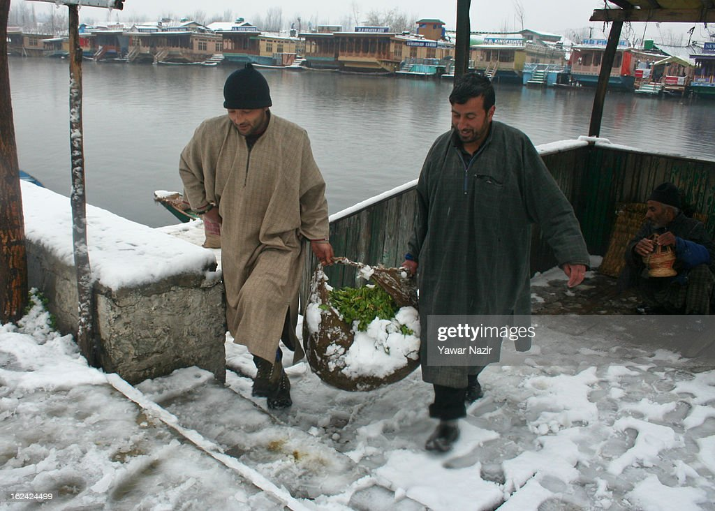 Kashmiri men carry vegetables on the bank of Dal lake after a snowfall on February 23, 2013 in Srinagar, Indian Administered Kashmir, India. Several parts of the Kashmir Valley, including the summer capital Srinagar, experienced fresh snowfall today, prompting the authorities to issue an avalanche warning and leading to closure of the Jammu-Srinagar Highway, the only road link between Kashmir and rest of India. (Photo by Yawar Nazir/Getty Images)2