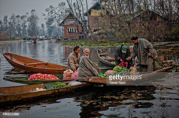 Kashmiri men gather with their boats laden with vegetables at the floating vegetable market on Dal Lake at dawn on November 12 2015 in Srinagar the...