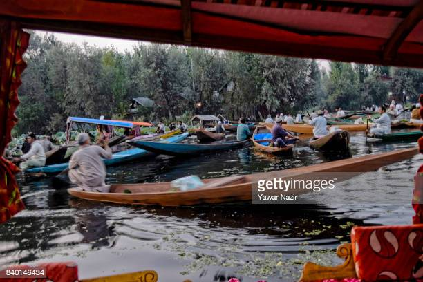 Kashmiri men gather with their boats laden with vegetables at the floating vegetable market on Dal Lake at dawn on August 28 2017 in Srinagar the...