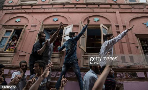 Kashmiri men hang onto a house wall and windows and shout profreedom slogans during funeral of a local rebel Sajad Gilkar Wednesday July 12 2017 in...