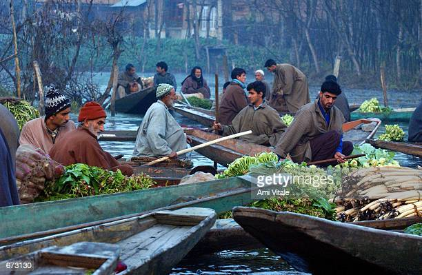 Kashmiri men sell their vegetables November 24 2001 at a floating market in the early hours before sunrise on Dal Lake in the troubled summer capital...