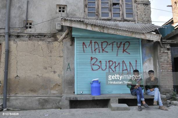 Kashmiri men sit next to graffiti that reads 'Martyr Burhan' in reference to the militant commander during curfew in Lal Chowk area on July 8 2017 in...