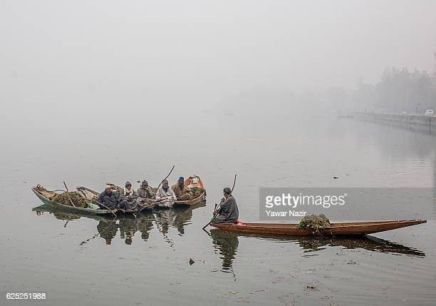 Kashmiri men take rest in their boats after extracting weeds from the Dal lake during a cold foggy day on November 23 2016 in Srinagar the summer...