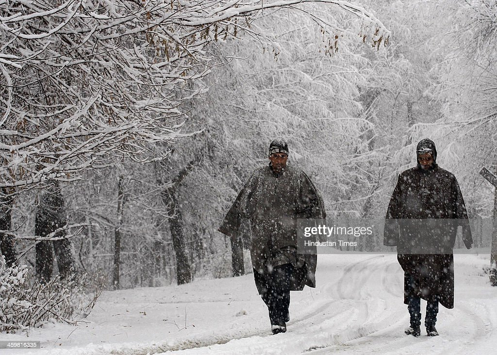 Kashmiri men walk on the road during a heavy snowfall on December 31, 2013 in Srinagar, India. Kashmir today received heavy snowfall in the beginning of its 40-day period of harsh winter. The strategic Srinagar-Jammu National Highway was closed in the morning due to heavy snowfall in Banihal and Patnitop sectors.