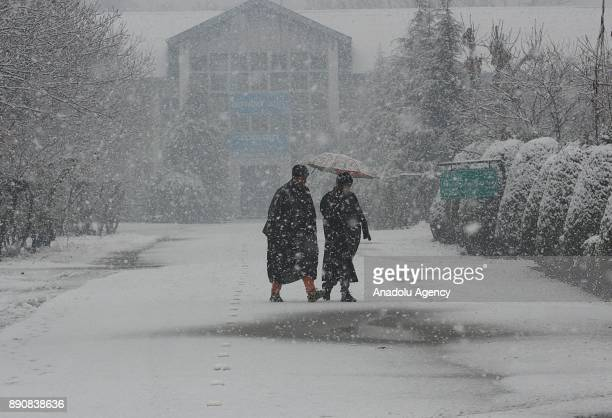 Kashmiri men walk on the snow covered road as it snows in Srinagar the summer capital of Indian controlled Kashmir on December 12 2017 Heavy snowfall...