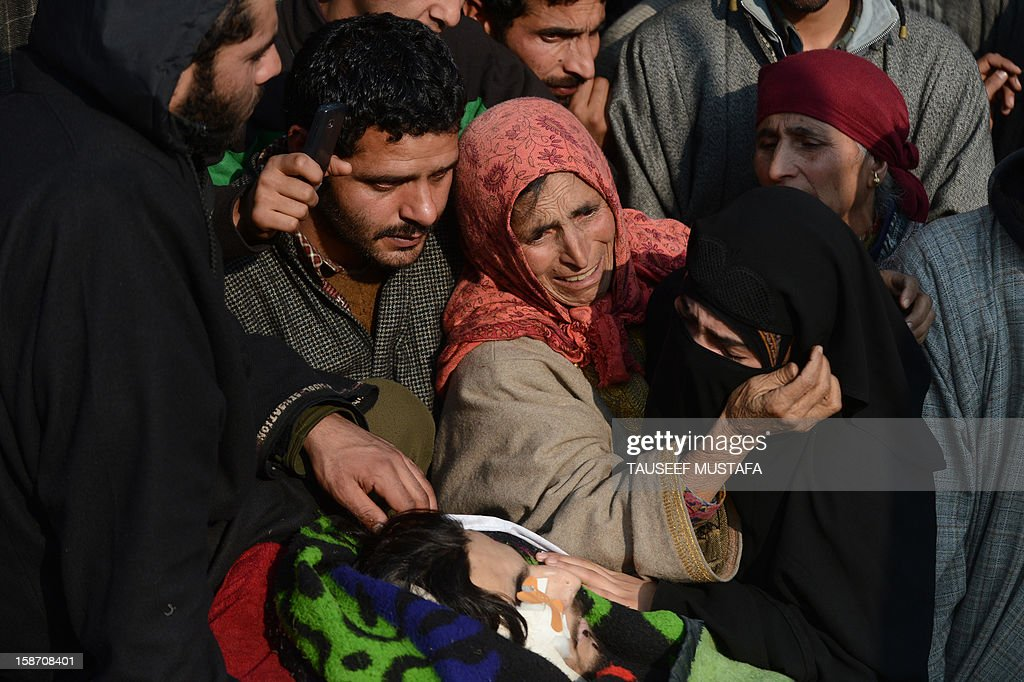 Kashmiri mourners including his mother (C) and sister (R) grieve during a funeral of alleged Pakistan-based Lashker-e-Toiba militant Mudasir Sheikh alias Mavia (L) a self styled 'district commander' and his Pakistani associate Tamim in Kulgam district of south Kashmir some 75kms from Srinagar on December 25, 2012. Security forces confronted the pair of rebels and in the ensuing gunbattle they and a policeman were killed. A police spokesman said that the two were implicated in an attack on The Silver Star Hotel in Srinagar and on an army convoy. AFP PHOTO/Tauseef MUSTAFA