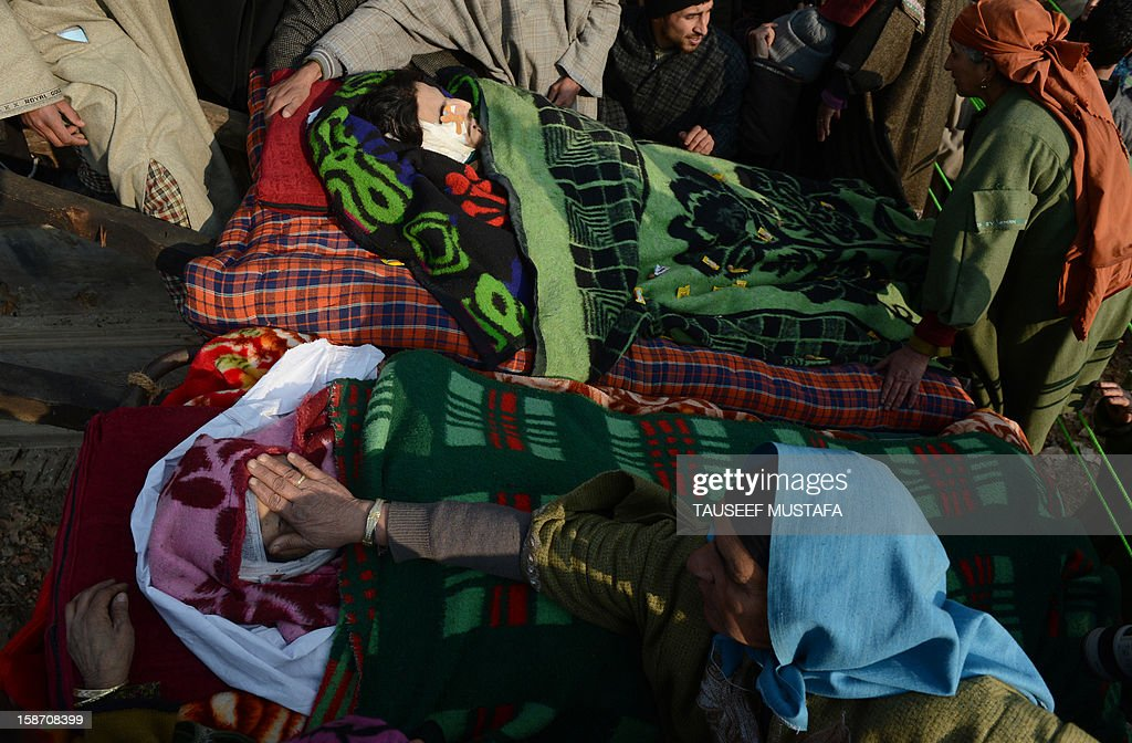 Kashmiri mourners look on during a funeral of alleged Pakistan-based Lashker-e-Toiba militant Mudasir Sheikh alias Mavia (L) a self styled 'district commander' and his Pakistani associate Tamim in Kulgam district of south Kashmir some 75kms from Srinagar on December 25, 2012. Security forces confronted the pair of rebels and in the ensuing gunbattle they and a policeman were killed. A police spokesman said that the two were implicated in an attack on The Silver Star Hotel in Srinagar and on an army convoy. AFP PHOTO/Tauseef MUSTAFA