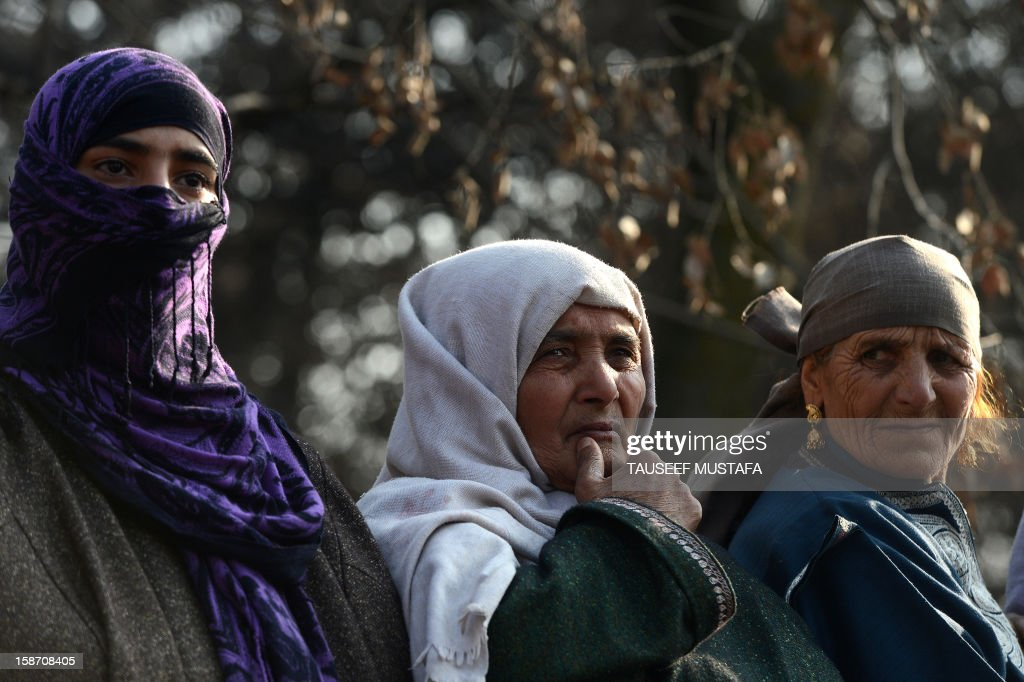 Kashmiri mourners look on during a funeral of alleged Pakistan-based Lashker-e-Toiba militant Mudasir Sheikh alias Mavia a self styled 'district commander' and his Pakistani associate Tamim in Kulgam district of south Kashmir some 75kms from Srinagar on December 25, 2012. Security forces confronted the pair of rebels and in the ensuing gunbattle they and a policeman were killed. A police spokesman said that the two were implicated in an attack on The Silver Star Hotel in Srinagar and on an army convoy. AFP PHOTO/Tauseef MUSTAFA