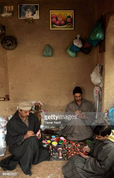Kashmiri Muslim artisans paint the final touches to products before before sending them to the market on December 15 2009 in Srinagar Kashmir India...