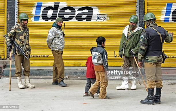 Kashmiri Muslim boys walk past Indian paramilitray troopers standing guard in Srinagar on February 10 2014 Political groups opposed to Indian rule in...
