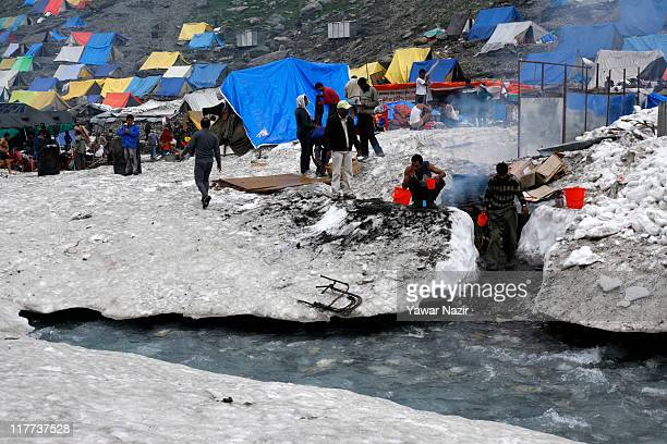 Kashmiri Muslim camp owners boil water on a traditional stove for the bathing purpose for Hindu pilgrims near Amarnath cave one of the most revered...