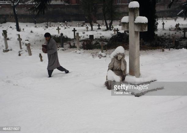 Kashmiri Muslim caretaker of Christian cemetery walks inside a graveyard during a snowfall on January 22 2014 in Srinagar Indian Administered Kashmir...