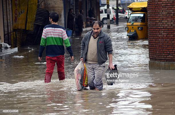 Kashmiri muslim carries his belongings in waterlogged city center Lal chowk in Srinagar the summer capital of Indian administered Kashmir on March...