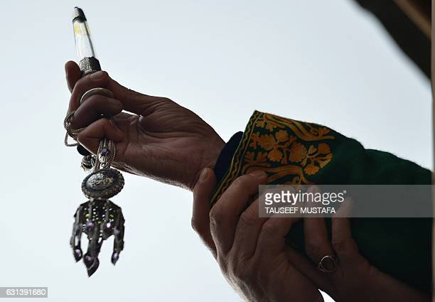A Kashmiri Muslim cleric displays a relic at the shrine of Sheikh Abdul Qadir Geelani in Srinagar on January 10 2017 Devotees are marking the urs or...