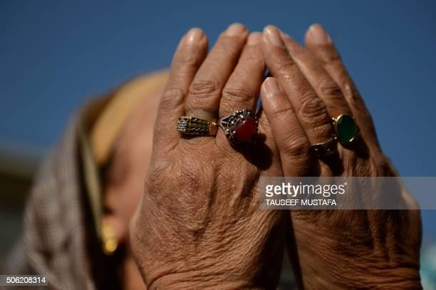 Kashmiri Muslim devotee offer prayers as a priest displays a relic at the shrine of Sheikh Abdul Qadir Geelani in Srinagar on January 22 2016...