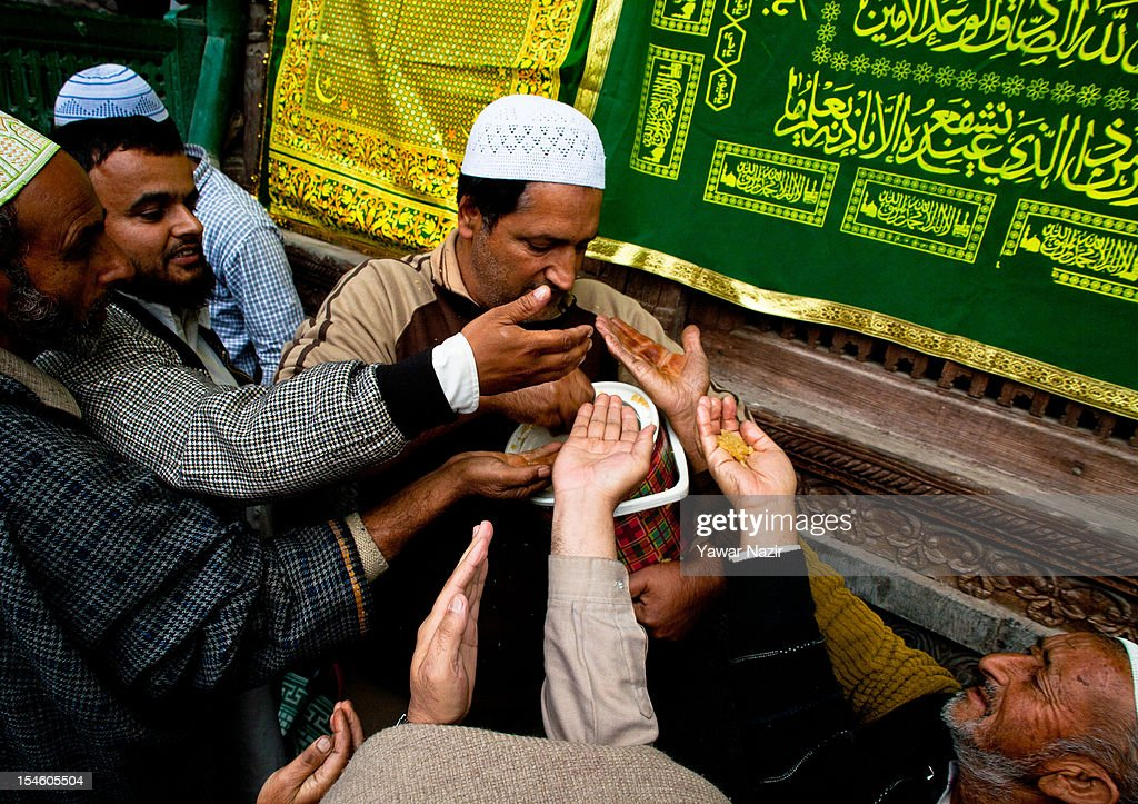 A kashmiri Muslim distribute sweet food among Muslim devotees at the shrine of Khaniqahi mullah during a festival on October 23, 2012 in Srinagar, the summer capital of Indian administered Kashmir, India. Thousands of Muslims thronged to the shrine of Mir Syed Ali Hamadan to commemorate the anniversary of the death of the Sufi saint, Hamadan. He is believed to be responsible for the spread of Islam in Kashmir. The shrine gains a special significance on 6th of Zilhaj (last month of Muslim calendar), the death anniversary of Mir Syed Ali Hamadan. On this day, devotees visit the shrine in large numbers to pay a tribute to saint Hamadan.