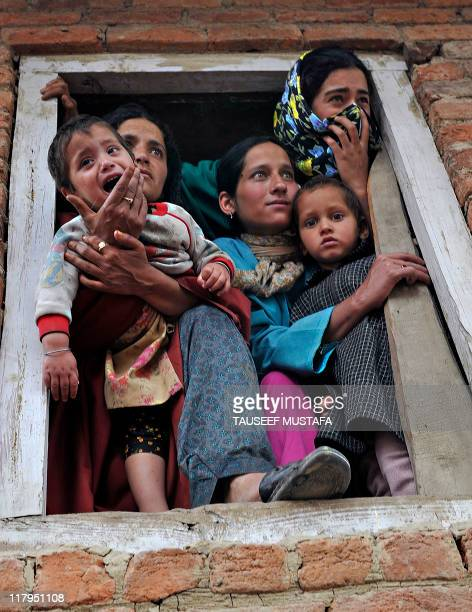 A Kashmiri Muslim family weeps as they watch the funeral of alleged Pakistanbased JaisheMohammad militants Qari Zubair and his bodyguard Muhammed...