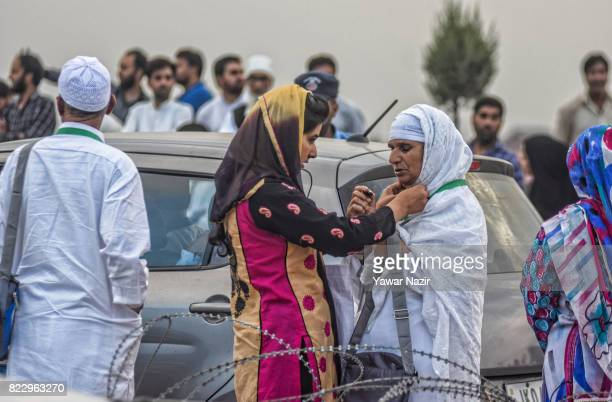 Kashmiri Muslim girl adjust head scarf of her mother as she departs for the annual Hajj pilgrimage on July 26 2017 in Srinagar the summer capital of...
