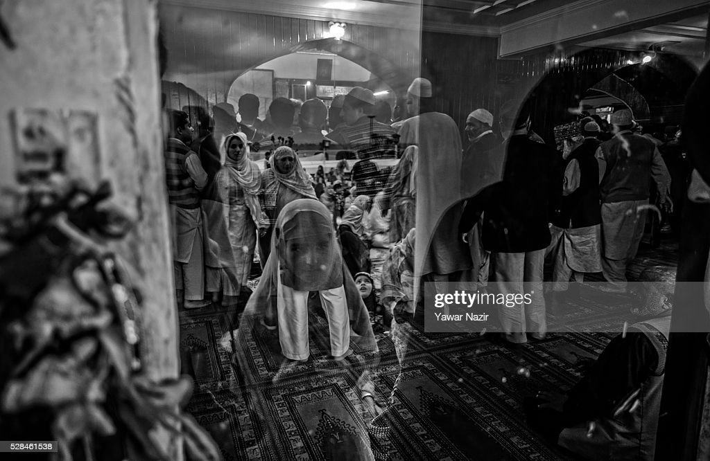A Kashmiri Muslim girl is reflected on the glass as she prays outside the Hazratbal Shrine on the MehrajuAlam which marks ascension day the journey...