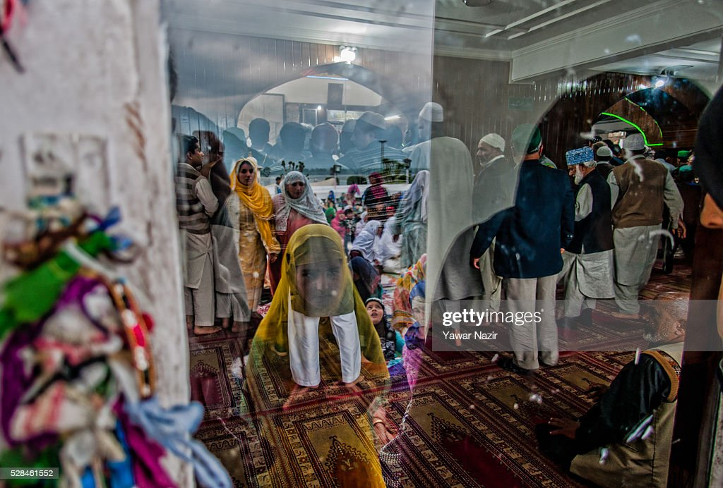 Kashmiri Muslim girl is reflected on the glass as she prays outside the Hazratbal Shrine on the MehrajuAlam which marks ascension day the journey...